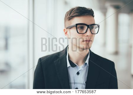 Close up smiling young businessman wearing eyeglasses looking away