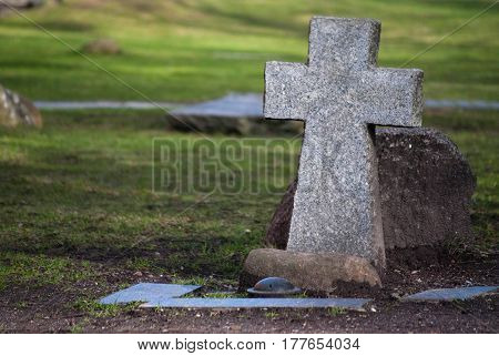 Old stone cross on the bed of honor. Memorial for those who killed during the military raides of the British Army on Koenigsberg in 1944 Kaliningrad Russia