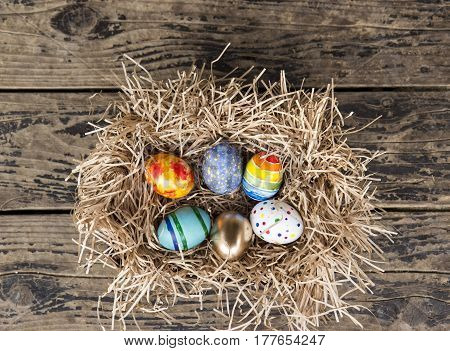 Easter colorful eggs in the nest on wooden background