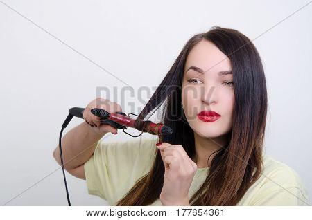 a girl does a hair-do a rectifier for hair