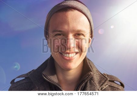 portrait of a young handsome smiling man wearing a coat and cap