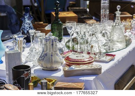 Nice France - May 17 2014: Antiques put on sale during the flea market which was held on one of the squares in the city. On the table many glass items and other items for tableware can be seen