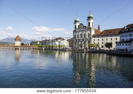 Lucerne Switzerland - May 04 2016: Jesuit Church dominates at the banks of the River Reuss in the area of the old town. A little further Octagonal tower and the Roofed Chapel Bridge can be seen.