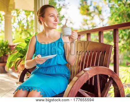 Young woman in blue dress enjoying a cup of beverage. Outdoor portrait. Coffee and tea drinking conception.