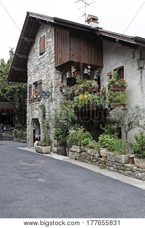 Yvoire France - May 24 2013: Townhouse built of stone is located along the street in medieval town. The building is decorated with many plants.
