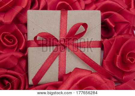 Gift box with red satin ribbons and red satin roses in the background