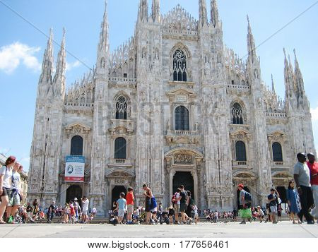 MILAN, ITALY - AUGUST 12, 2016: People walking near Piazza Duomo di Milano cathedral in Milan, Italy from the low angle. Famous popular travel landmark in Europe