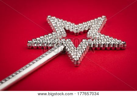 side low angle view of crystal shiny star wand on red background selective focus