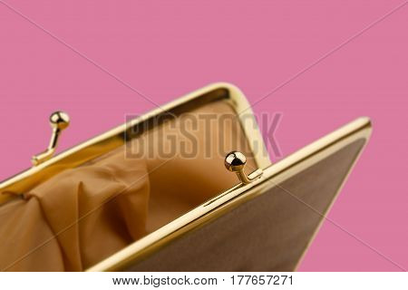 macro detail of open female cream colored vintage wallet with golden metal enclosure on pink background