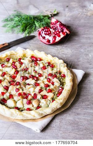 Puff pastry pie with fish cod fillet, spinach, dill, pomegranate seeds and cream cheese, selective focus
