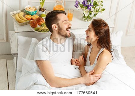 Relaxed Couple in Bed in bedroom at home at morning and colorful breakfast