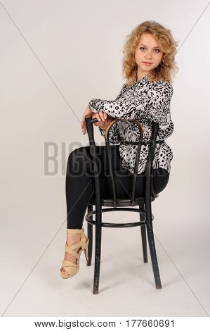 Young beautiful woman sitting on chair over white background