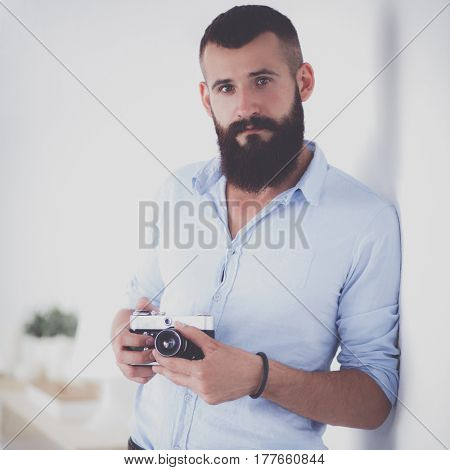 Young beard man holding a camera while standing against white background