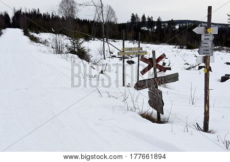 Lot of confusing signs where a snowmobile trail cross the road picture from the North of Sweden.