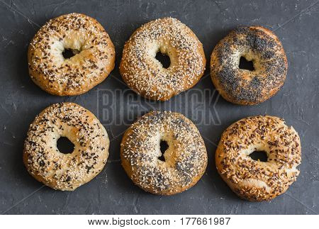 Homemade bagels with a variety of seeds on a gray background top view. Food background