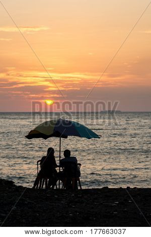 A romantic silhouetted couple sit at a basic patio table with rainbow parasol watching the sunset out to sea with an island on the horizon.
