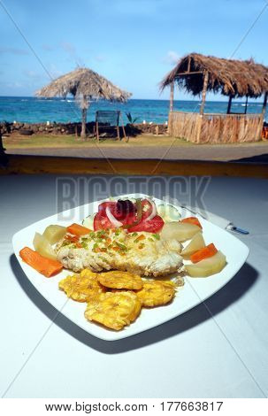 fresh fish fillet with tostones salad and native vegetables is seen with Caribbean background in Big Corn Island Nicaragua