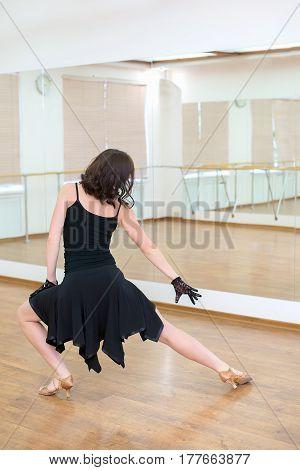 Girl in black dress beautiful dancer seen from behind at dance class