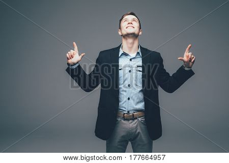 Young Handsome Businessman Pointing With Finger Up On Grey