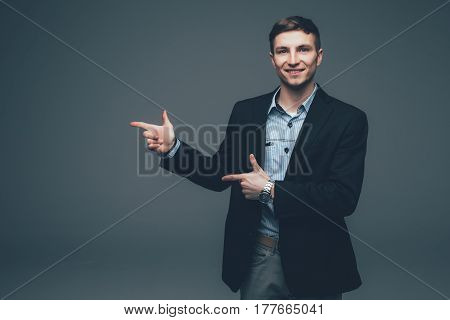 Young Handsome Businessman Pointing With Finger On Side On Grey