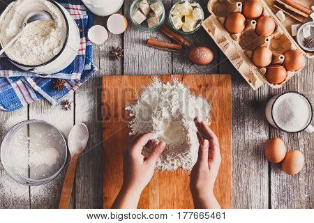 Making sweet dough top view. Baker hands sprinkle flour. Cooking ingredients for pastry on rustic wood, culinary classes or recipe concept.