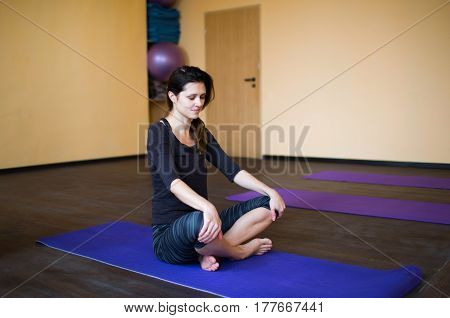 beautiful young woman resting after doing yoga exercises sitting meditating relaxing with closed eyes