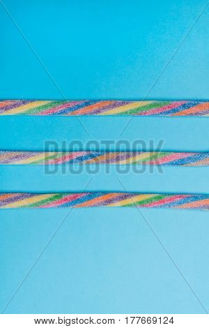 Colorful tasty licorice candies. Homemade twisted colorful twisted licorice candies over blue background