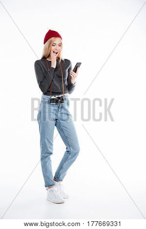 Full length of a young excited woman photographer looking at mobile phone isolated over white background