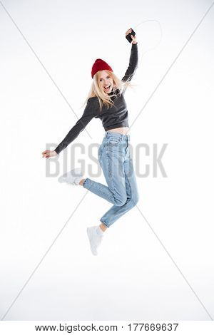 Full length portrait of an excited blonde girl in hat jumping with earphones