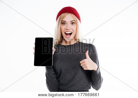 Portrait of an excited blonde woman holding blank screen tablet computer and showing thumb up isolated on a white background