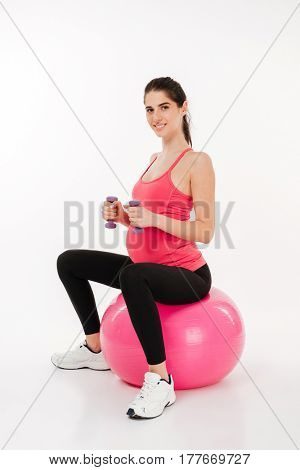 Young smiling woman doing pregnancy exercise with fitness ball and dumbbells isolated over white