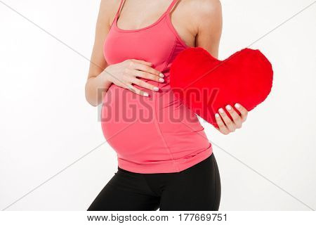 Close up portrait of a female pregnant belly with pillow heart isolated on white background