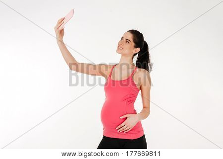 Portrait of a smiling brunette pregnant woman in sport wear taking selfie isolated on white background
