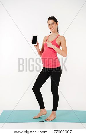Full length portrait of a smiling healthy pregnant woman standing on sport mat and showing pointing at blank screen mobile phone isolated on white background