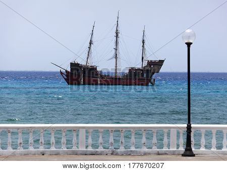 The old style wooden ship drifting by San Miguel town (Cozumel island Mexico).