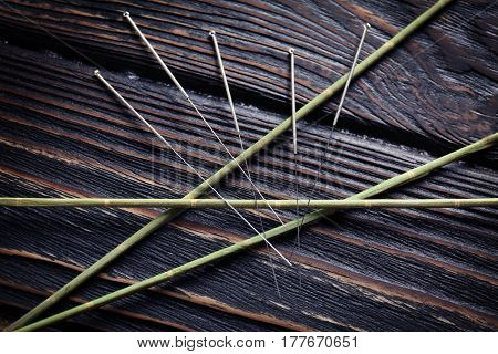 Acupuncture needles on wooden background