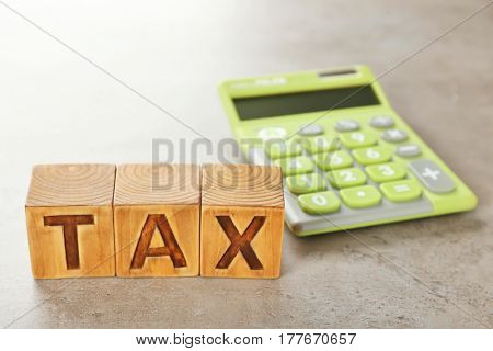 Wooden cubes with word TAX and calculator on grey background