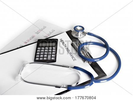 Health insurance concept. Clipboard, calculator and stethoscope on light background