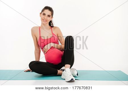 Portrait of a smiling pregnant woman sitting on the mat isolated on white background