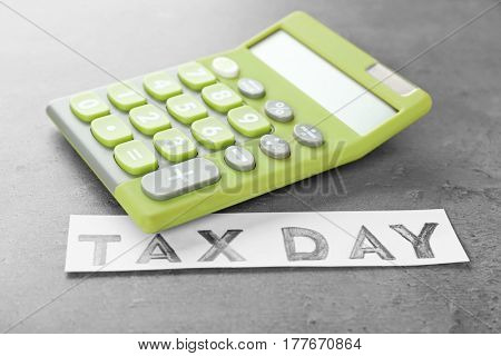 Green calculator and text TAX DAY on grey background