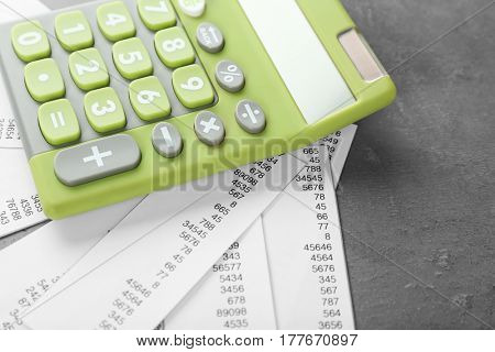Green calculator and receipts on grey background