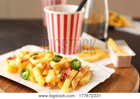 Cheese fries and cup of soda water on wooden board