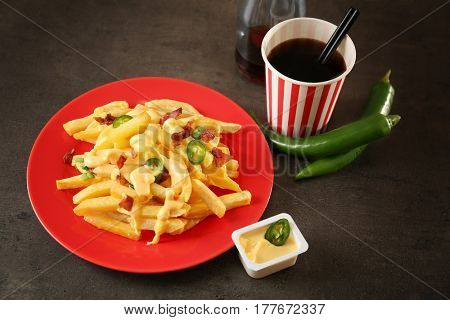 Plate with cheese fries and cup of soda water on table
