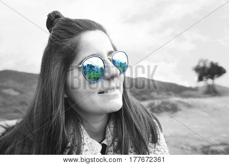 the reflection of Meteora Greece on woman's sunglasses