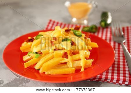 Plate with delicious cheese fries and sauce on table