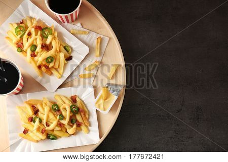 Tray with delicious cheese fries and cups of soda water on table