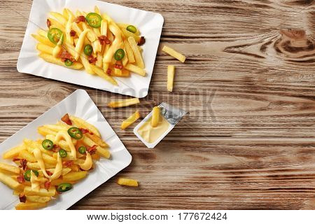 Delicious cheese fries on wooden table