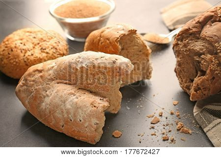 Bread crumbs and broken loafs on grey background