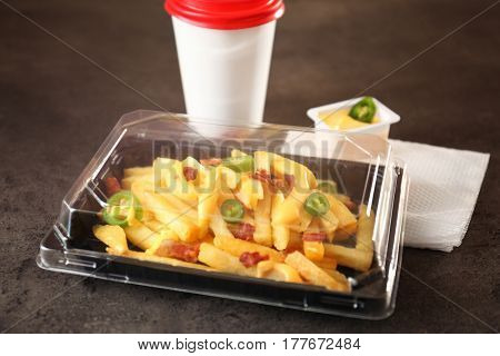 Plastic box with cheese fries and cup on table
