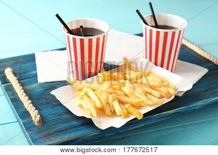 Tasty cheese fries and cups of soda water on wooden board